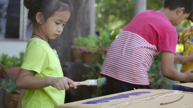 アジアの若い女の子と彼の兄弟は、絵筆で紙箱のカートンに絵を描いています ビデオ