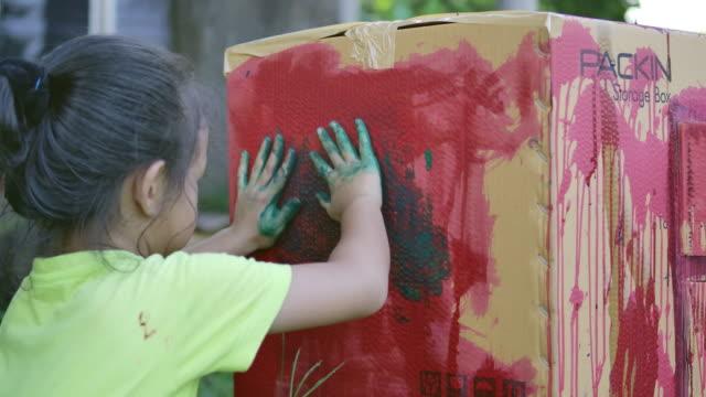 アジアの若い女の子は、彼女の手、子供の抽象芸術学習活動で紙箱に色を描いています ビデオ
