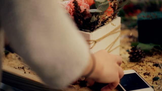 an aspiring florist uncertainly lays fir cones on a pot with a flower video