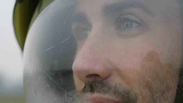 астронавт одетый человек использует смартфон для вызова и отправки сообщений. астронавт улыбается, глядя на телефон в руке. концепция: теле - white background стоковые видео и кадры b-roll