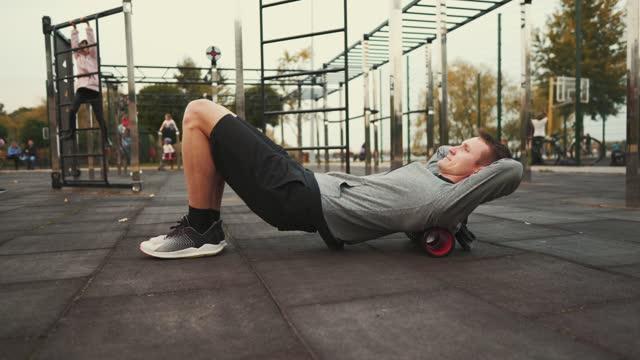 un atleta che fa esercizi su un rullo di schiuma per il massaggio muscolare ad alta densità per il mal di schiena. rullo per il punto di innesco della fisioterapia e l'esercizio fisico. massaggio profondo dei tessuti, dolore, yoga, muscolo delle gambe. - dorso umano video stock e b–roll