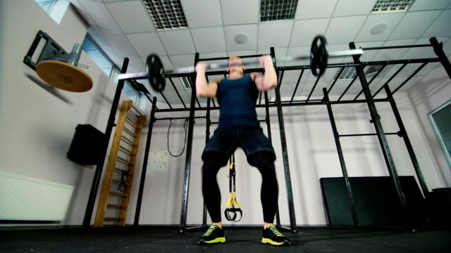 An athlete trains with a barbell. Low angle shot video