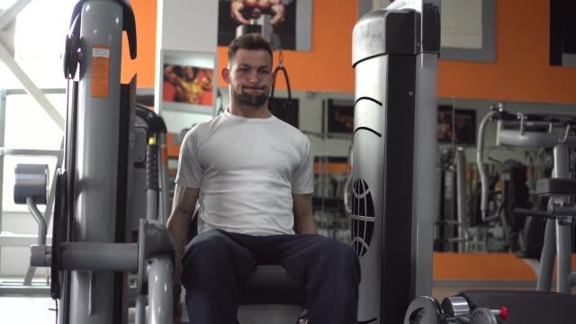 vídeos de stock, filmes e b-roll de um homem atlético engajado em exercício de perna no treino de ginástica - comodidades para lazer