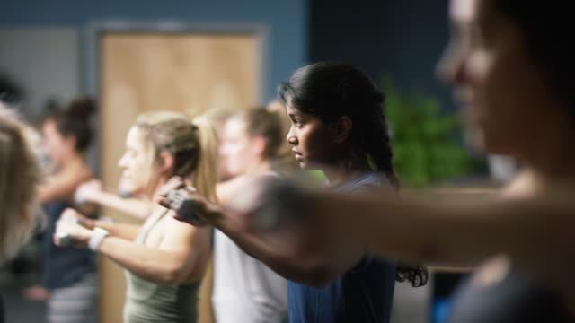 eine attraktive asiatische indische frau in ihren zwanzigern führt schulter übungen mit hanteln mit anderen frauen in einem studio barre übung - fitnessausrüstung stock-videos und b-roll-filmmaterial