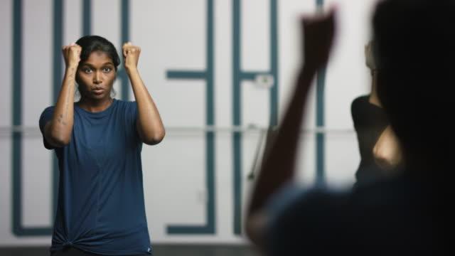 en attraktiv asiatisk indisk kvinna i tjugoårsåldern med armarna utsträckta utför skuldra övningar med en grupp kvinnor i en framför en spegel på en barre motion studio - balettstång bildbanksvideor och videomaterial från bakom kulisserna