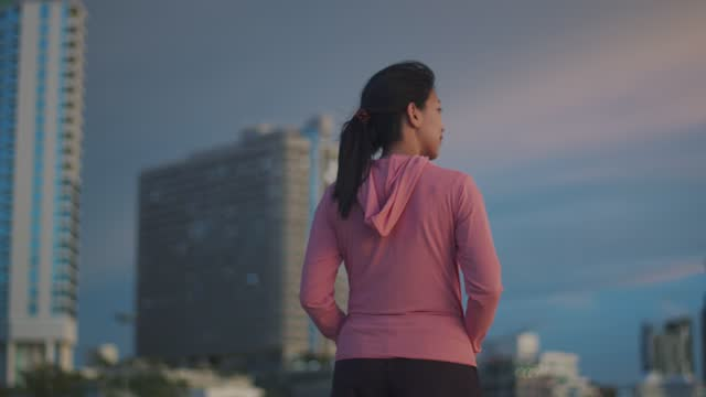 An attractive Asian woman runner looks at the sea view while standing on the beach having a hotel building background.