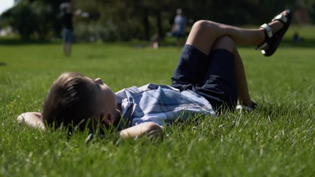 an attractive boy lies in a park on the grass having a good mood during the day in sunny weather. slow motion - leżeć filmów i materiałów b-roll