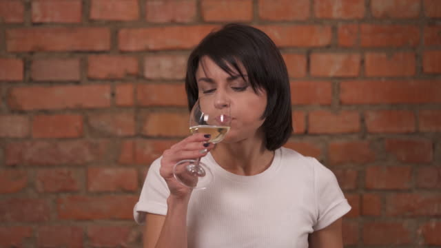 an attractive brown-haired woman stands on brick wall background and smells the white wine. she tastes the wine and does not like it. - gusto aspro video stock e b–roll