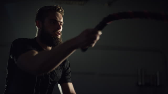 An Attractive Caucasian Man in His Twenties Climbs a Pegboard Wall in a Dramatically Lit Gym (wide shot) The Camera Tilts Up to Reveal an Attractive Caucasian Man in His Twenties with a Beard Doing Battle Rope Exercises in a Dramatically Lit Gym (medium shot) cross training stock videos & royalty-free footage