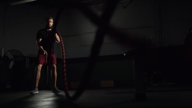 stockvideo's en b-roll-footage met een aantrekkelijke kaukasische man in zijn twintiger jaren met een baard voert battle rope oefeningen in een dramatisch verlicht sportschool (brede schot) - touw