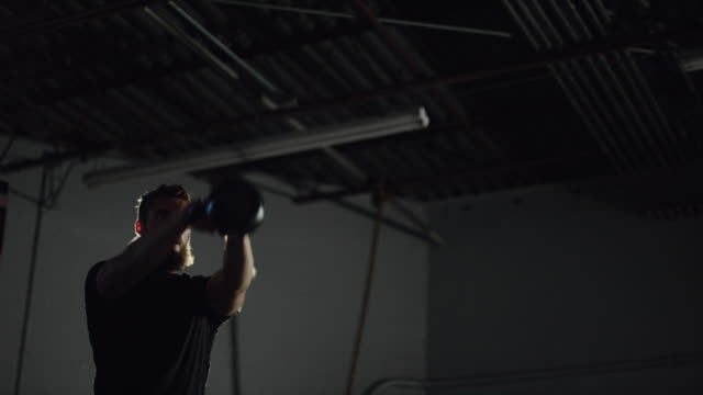an attractive caucasian man in his twenties with a beard performs kettlebell swings in a dramatically lit gym (wide shot) - giria filmów i materiałów b-roll