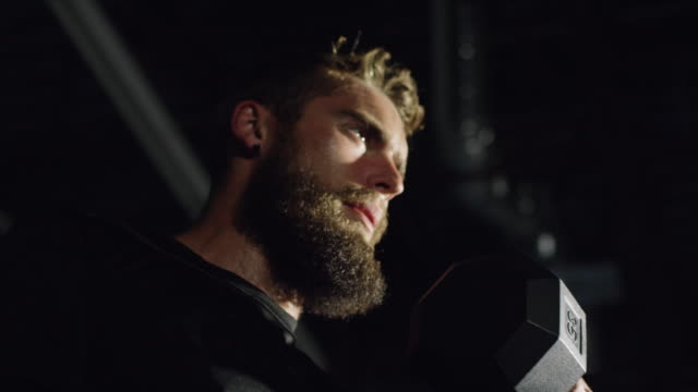 An Attractive Caucasian Man in His Twenties with a Beard Performs Bicep Curls with a Dumbbell in a Dramatically Lit Gym (tight shot) An Attractive Caucasian Man in His Twenties with a Beard Performs Bicep Curls with a Dumbbell in a Dramatically Lit Gym (tight shot) cross training stock videos & royalty-free footage