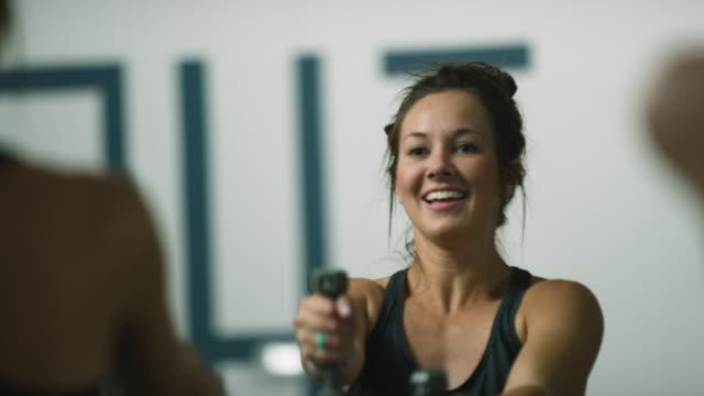 en attraktiv kaukasisk kvinna i tjugoårsåldern utför axelövningar med hantlar i en klass på en motion studio - balettstång bildbanksvideor och videomaterial från bakom kulisserna