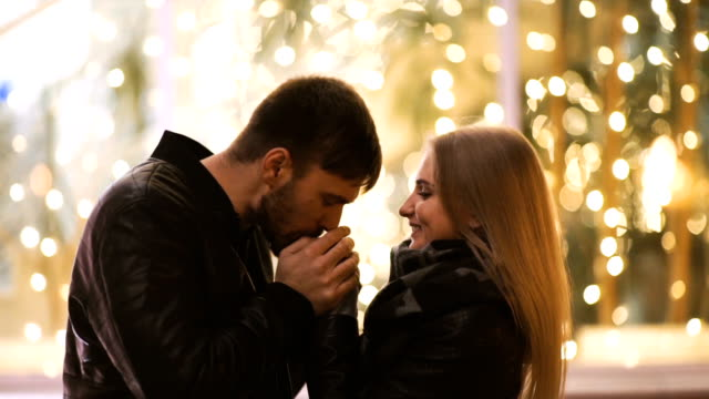 an attractive couple in love embrace and enjoy an intimate moment together, against the backdrop of city lights - date night stock videos & royalty-free footage