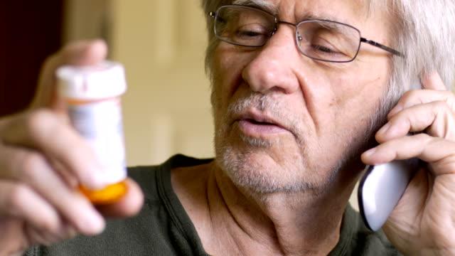 an attractive elderly senior calls in his medicine prescription on a flip phone - prescrizione medica video stock e b–roll