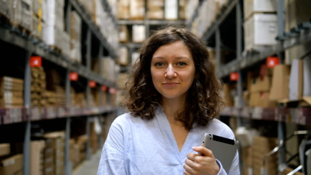 An attractive girl stands with a tablet in a warehouse between the shelves with goods, smiles and looks at the camera - vídeo