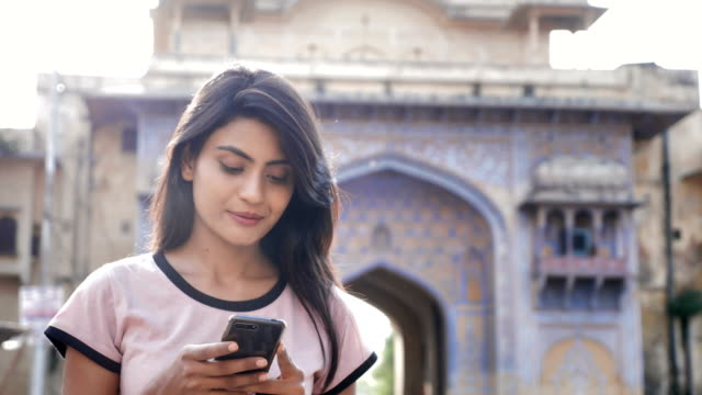 an attractive girl using smartphone or cellphone and walks on the busy town road - india video stock e b–roll