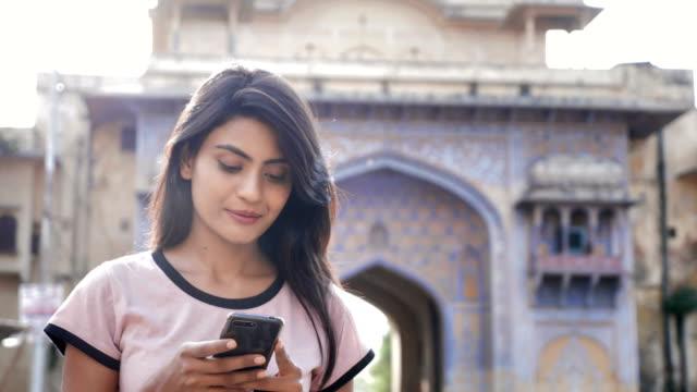 çekici bir kız akıllı telefon veya cep telefonu ve yürüyüşler meşgul şehir arazide kullanmak - hindistan stok videoları ve detay görüntü çekimi