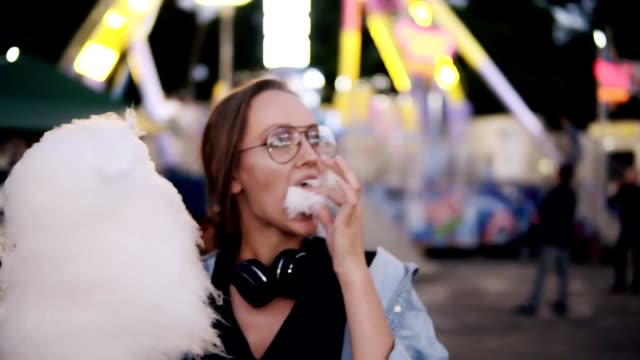 An attractive girl walking in the amusment park, eats white cotton candy. Girl wearing casual clothes, headphones on her neck and glasses. Evening dusk An attractive girl walking in the amusment park, eats white cotton candy. Girl wearing casual clothes, headphones on her neck and glasses. Evening dusk. cotton candy stock videos & royalty-free footage