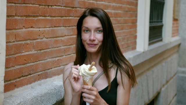 An attractive happy girl eating a tasty ice-cream cone during her vacation in Madrid on sunny summer day. Spain. 4K