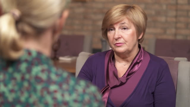 An attractive mature woman facing the camera and talking to another woman sitting back to the camera. She shares her opinion, shrugs shoulders a bit, points to herself, and in the end, sighs a little An attractive mature woman facing the camera and talking to another woman sitting back to the camera. She shares her opinion, shrugs shoulders a bit, points to herself, and in the end, sighs a little. Interviewing. job interview stock videos & royalty-free footage