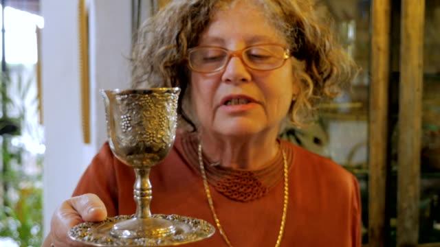 vídeos y material grabado en eventos de stock de una atractiva mujer judía mayor explica la copa kiddush - pascua judía