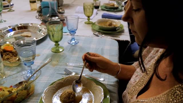 vídeos y material grabado en eventos de stock de una mujer atractiva comiendo sopa de bolas matzo - pascua judía