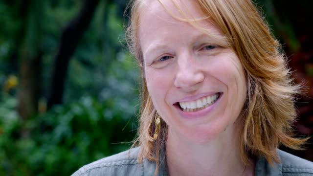 una donna attraente con i capelli rossi sorride per la fotocamera fuori durante il giorno - capelli rossi video stock e b–roll