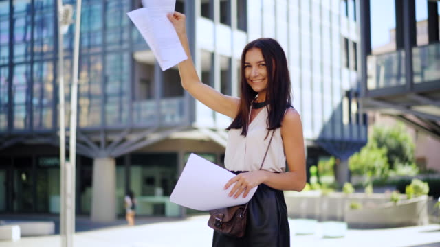 an attractive young female team leader holds in hand financial report or financial plans and presenting to his team. portrait of a successful happy business woman - financial planning stock videos & royalty-free footage