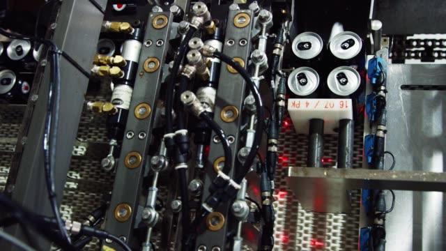 eine automatisierte verpackungsmaschine bereitet aluminiumkannen für den versand und vertrieb in einer indoor-fertigung vor - aluminium stock-videos und b-roll-filmmaterial