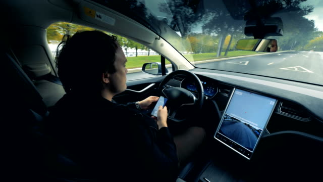 an automatic automobile is moving along the road with its driver sitting inside - self driving cars stock videos & royalty-free footage