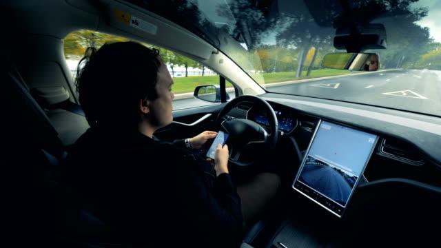 自動車は、そのドライバーが中に座って道路に沿って移動しています - 自動運転車点の映像素材/bロール