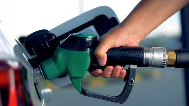 An automobile is getting refueled by a petrol pistol An automobile is getting refueled by a petrol pistol. 4K refueling stock videos & royalty-free footage