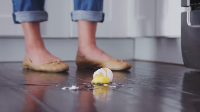 An egg falling to the kitchen floor and breaking on the wooden floorboards, low angle, slow motion