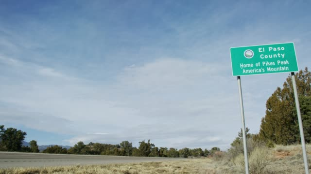 "an el paso county road sign (""home of pikes peak america's mountain"") next to a road under a partially cloudy sky in colorado - road signs stock videos and b-roll footage"