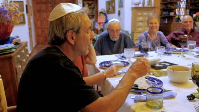 vídeos y material grabado en eventos de stock de un anciano explica el significado de matzah en un seder - pascua judía