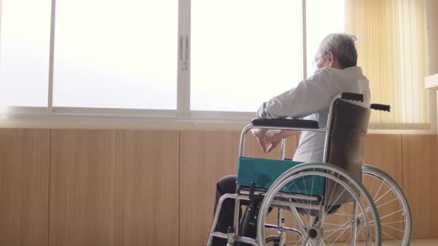 vídeos de stock e filmes b-roll de an elderly asian person is sitting on a wheelchair. - old men window