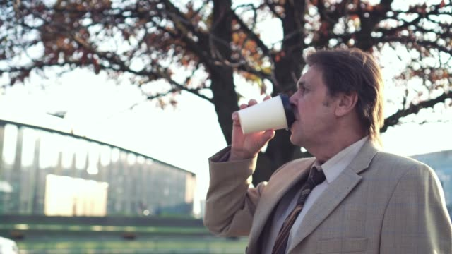 An elderly businessman in a business suit and tie is drinking coffee near a busy road. The camera moves around video