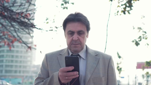 An elderly businessman in a business suit and tie stands in the city and browses the Internet using an application on a smartphone. The camera moves around video