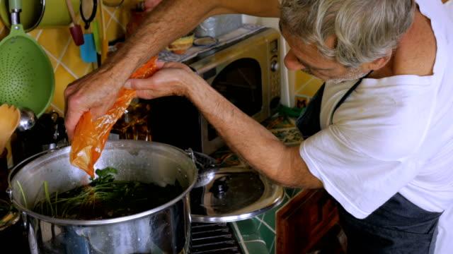 vídeos y material grabado en eventos de stock de un cocinero anciano añade pimentón de una bolsa de plástico a una olla de sopa de pollo - pascua judía
