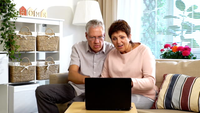 An Elderly Couple Communicates with Laptop Video Call video