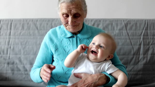 An elderly grandmother holds a small grandson in her arms and plays with him. video