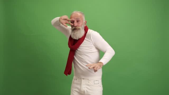 緑の背景に楽しい踊りをする年配の男性。 - あごヒゲ点の映像素材/bロール