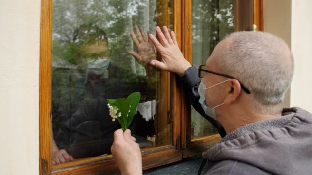 an elderly man in an anti-virus mask with lily of the valley flowers come to visit his elderly friend, who is in self-isolation. communication through the window glass. - hand on glass covid video stock e b–roll