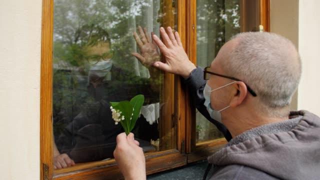 en äldre man i en anti-virus mask med lily of the valley blommor kommer att besöka sin äldre vän, som är i självisolering. kommunikation genom fönsterglaset. - dejta bildbanksvideor och videomaterial från bakom kulisserna