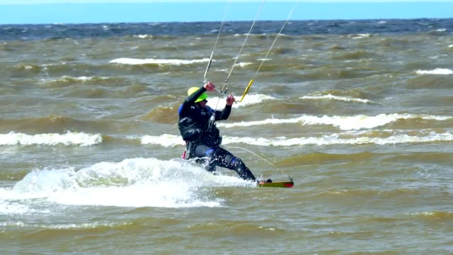 SLOW MOTION: An elderly man is engaged in kiting. He beautifully rides a kite on the waves of the pond. Strong wind blows. A man likes to practice kite in extreme weather. Pensioners on active rest. Cold autumn weather video