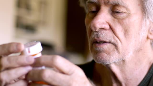 vídeos y material grabado en eventos de stock de un anciano lee en voz alta las instrucciones de sus botellas de medicamentos recetados - receta instrucciones