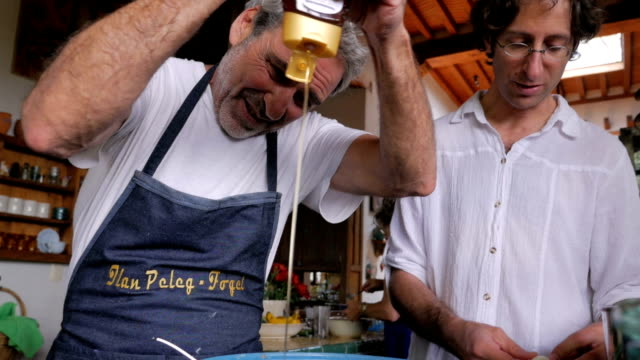 An elderly man squeezing honey into a bowl while another man peels an egg video
