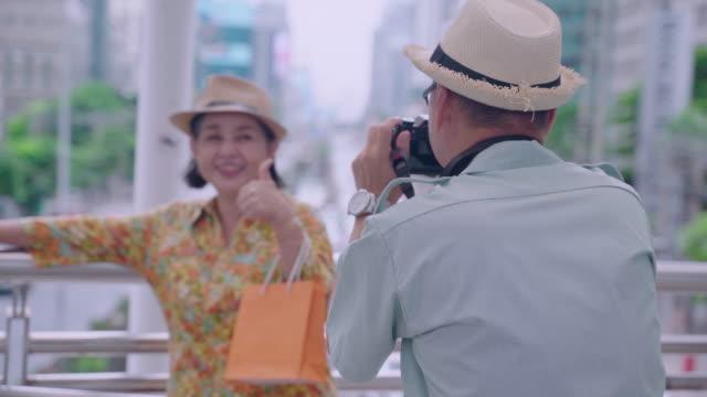ファンと一緒に写真を撮る年配の男性は、タイの首都を見下ろすテラスの歩道でポーズをとります。 - シニア点の映像素材/bロール