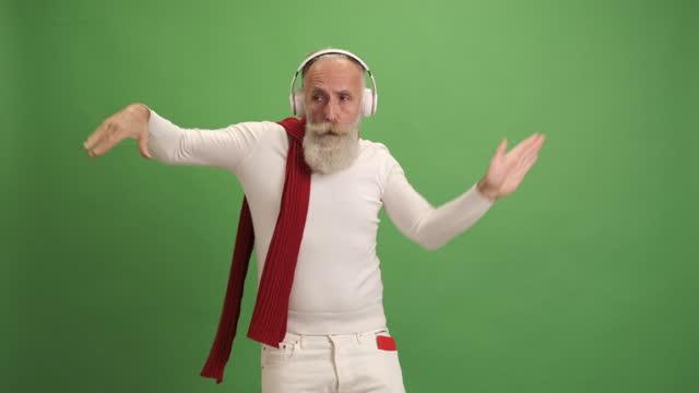 サンタクロースのように見える年配の男性は、スマートフォンで音楽を聴き、踊り、歌います。緑色の背景に.1人。 - あごヒゲ点の映像素材/bロール
